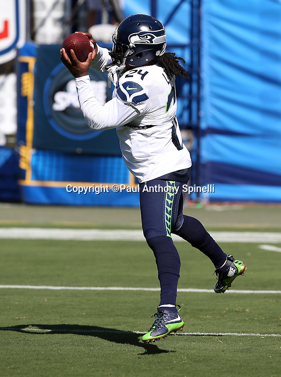 Seattle Seahawks running back Marshawn Lynch (24) leaps and catches a pass while warming up before the 2015 NFL preseason football game against the San Diego Chargers on Saturday, Aug. 29, 2015 in San Diego. The Seahawks won the game 16-15. (©Paul Anthony Spinelli)