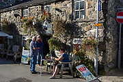 Pub drinkers and smokers enjoy evening sunshine outside the Torrent Walk pub, on 12th September 2018, in Dolgellau, Gwynedd, Wales.