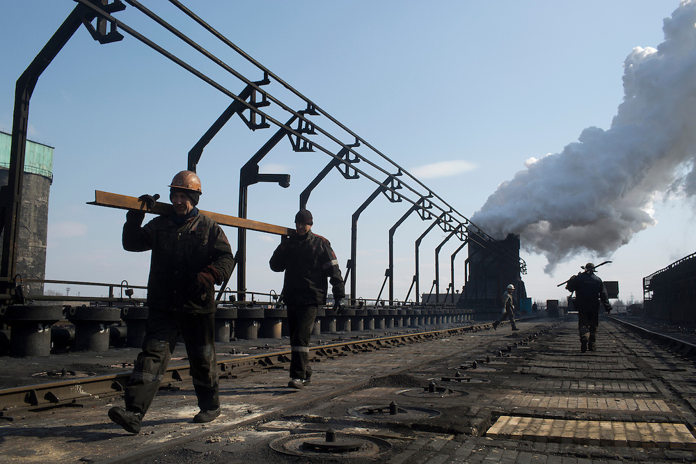 Workers carry material at the Metinvest Coke Plant on March 18, 2015 in Avdiivka, Ukraine. Shells have hit the property of the plant over 150 times, including multiple hits on the plant itself.