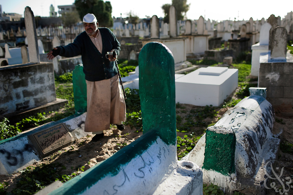 A crypt keeper at the al Bariyah cemetery points out the recently green painted graves of the Samouni family members December 19, 2009 in Gaza City, Gaza. The Samouni family is synonymous with the 22 day Israeli offensive in Gaza last year during which 29 members of the family were killed in the Zeitoon district of Gaza City. A year later, Palestinians across the tiny strip continue to struggle daily in various ways economically, physically, and emotionally. .