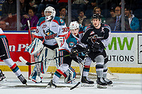 KELOWNA, CANADA - FEBRUARY 16: Jared Dmytriw #22 of the Vancouver Giants is checked by Kyle Crosbie #25 as Roman Basran #30 of the Kelowna Rockets defends the net against the Vancouver Giants  on February 16, 2019 at Prospera Place in Kelowna, British Columbia, Canada.  (Photo by Marissa Baecker/Shoot the Breeze)
