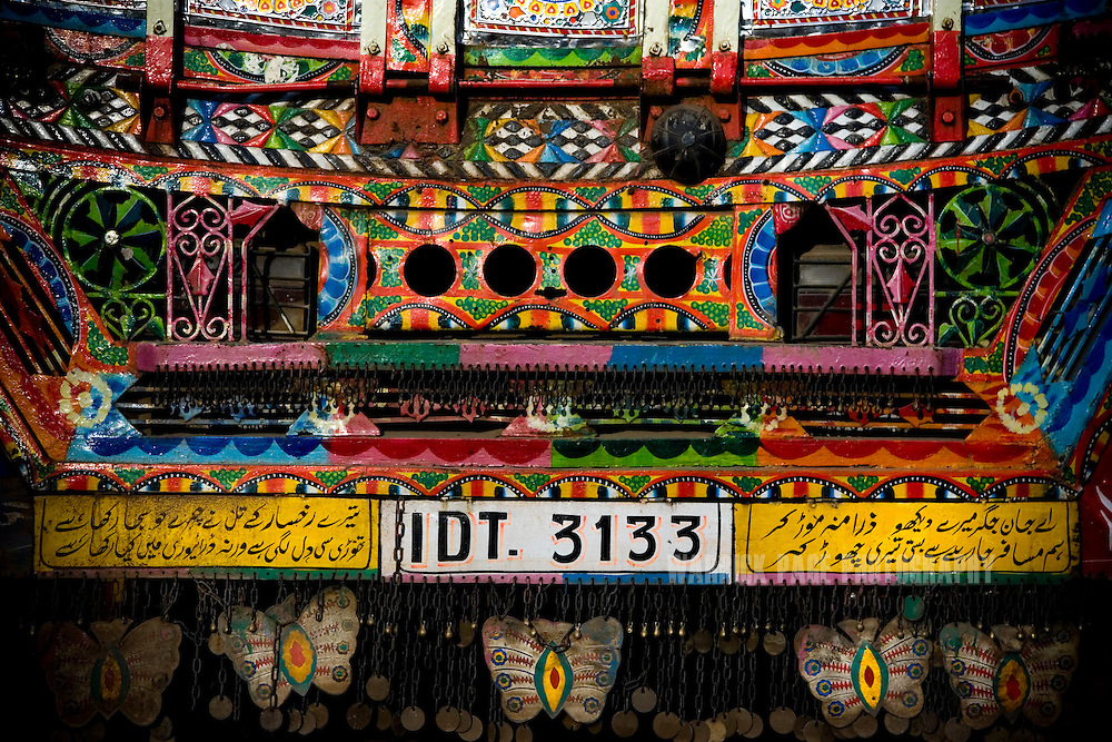 RAWALPINDI, PAKISTAN - OCTOBER 9: Urdu poetry adorns the rear of a garishly painted truck at a painting and repair yard, October 9, 2008, in Rawalpindi, Pakistan. The heavily adorned Bedford trucks have become a national icon and cost upwards of one million rupees (USD$12,500) for a full makeover. Much of the artwork consists of a cultural mix of religious and secular, Pakistani film and music stars, cricket legends, romanticized military imagery of F-16 fighter jets and Ghauri missiles, the Prophet's winged horse, Buraq, and dreamlike scenes of wooded lakes and snow-capped mountains and exotic animals. (Photo by Warrick Page)