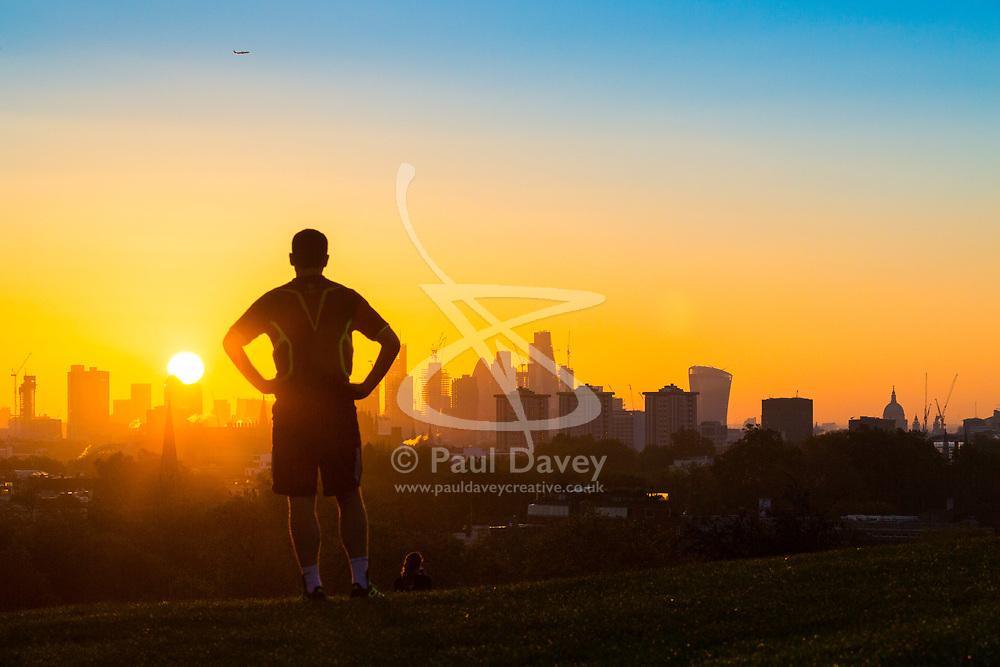 London, October 27 2017. The sun emerges from behind the skyscrapers as the day breaks over London, seen from Primrose Hill. © Paul Davey