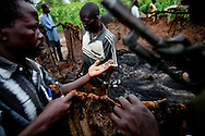 "Patrolling ""arrow boys"" inspect a house burnt down by the LRA outside of Tambura on May 23, 2010. The ""arrow boys"" are a self defence force that hs sprung up in Western Equatoria to defend against the LRA."