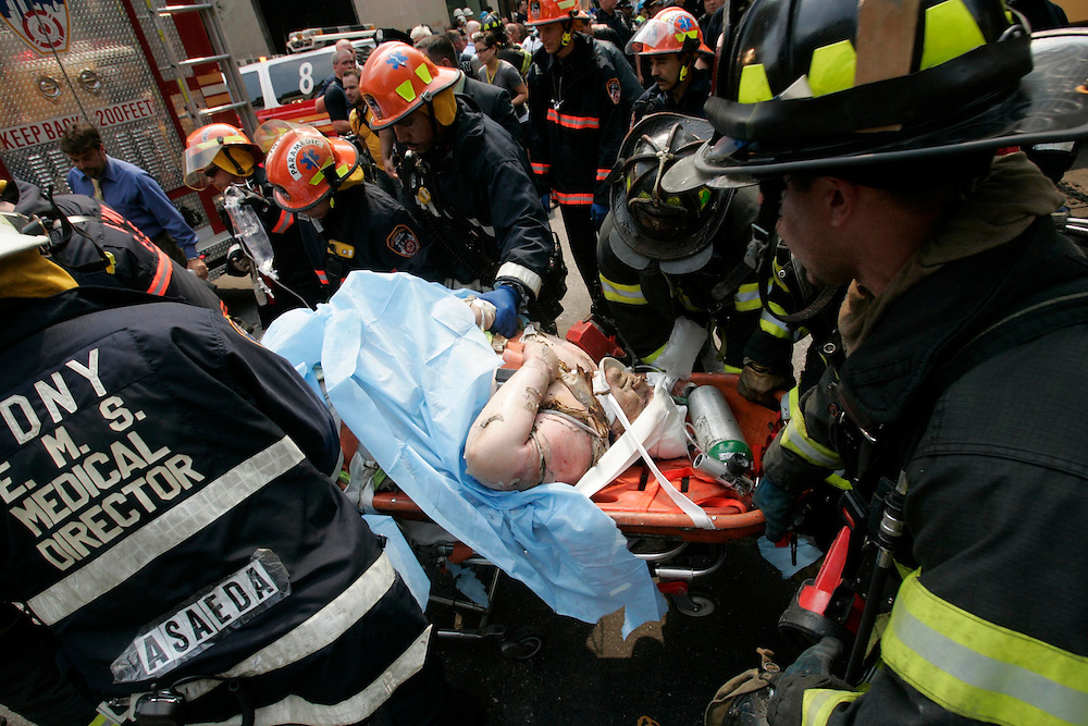 Rescue workers treat an injured man at the  scene of an explosion that caused the collapse of a building in New York, July 10, 2006.