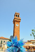 Beautiful, modern glass sculpture in front of a  traditional tower in a square in Murano, Venice, Italy.