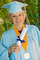 Senior graduate holding diploma outside portrait