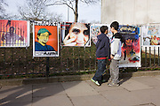 Young boys look at graphic posters as Libyan exiles protest outside their London embassy.
