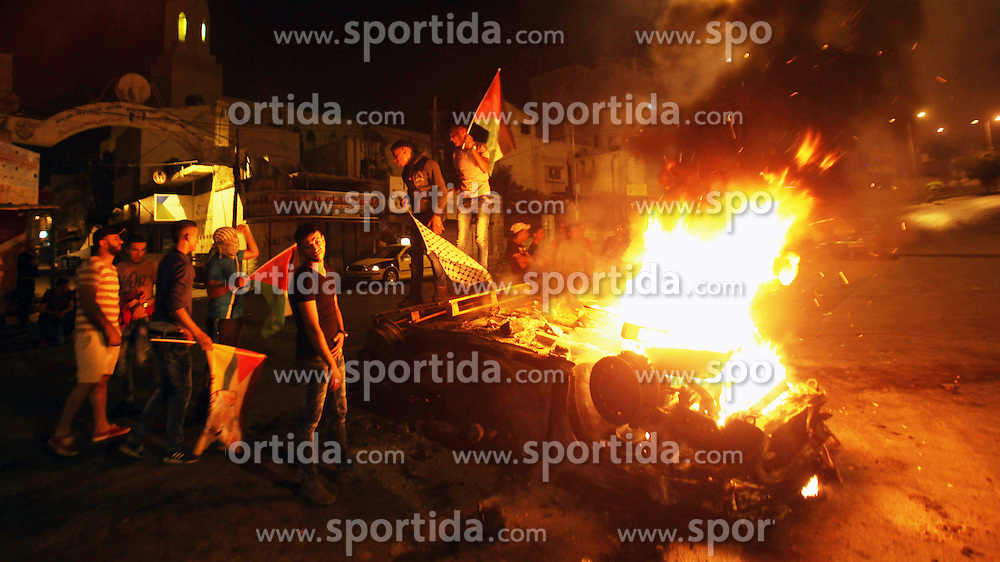 18.10.2015, Nablus, PSE, Gewalt zwischen Pal&auml;stinensern und Israelis, im Bild Zusammenst&ouml;sse zwischen Pal&auml;stinensischen Demonstranten und Israelischen Sicherheitskr&auml;fte // Palestinian youth stand next to a burning car belonging to an Israeli settler, that was set on fire by Palestinians as it entered the northern Palestinian West Bank city of Nablus, early on October 18, 2015, to visit and pray at Joseph's Tomb, a biblical figure from the book of Genesis, without the authorization of the Israeli army. The Israeli army arrested five settlers for entering the Palestinian territory without prior permission and escort, and evacuated the rest safely in coordination with Palestinian police in the area, Palestine on 2015/10/18. EXPA Pictures &copy; 2015, PhotoCredit: EXPA/ APAimages/ Nedal Eshtayah<br /> <br /> *****ATTENTION - for AUT, GER, SUI, ITA, POL, CRO, SRB only*****