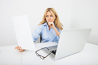 Young businesswoman reading document in office