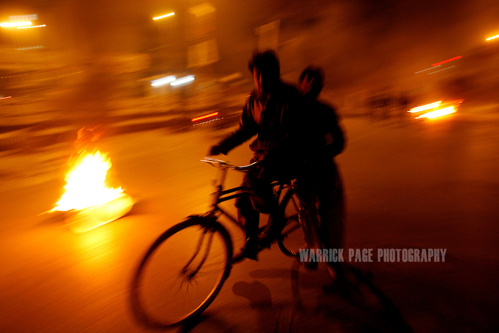 RAWALPINDI, PAKISTAN - DECEMBER 27: A man rides his bicycle near tires set alight by rioters enraged by the assassination of former prime minister, Benazir Bhutto, on December 27, 2007.The opposition leader has died from a bullet wound to the neck after speaking at a rally in the northern city where an estimated 15 people were left dead by the explosion, a party official and Bhutto's husband have been quoted as saying. (Photo by Warrick Page)
