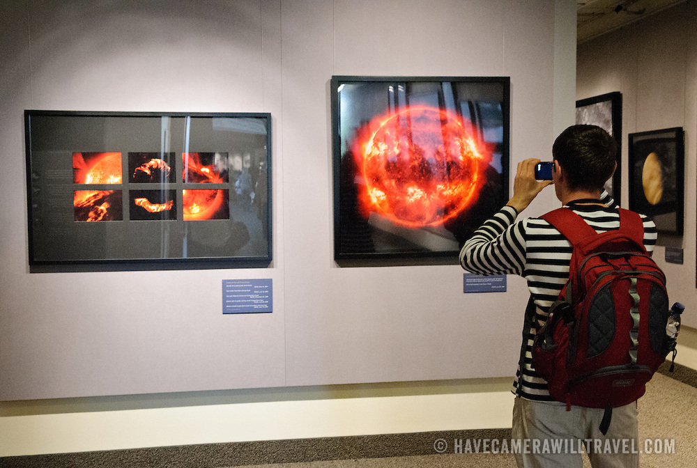 A visitor takes a photo of images of the sun at Michael Benson's photographic exhibit, Beyond: Visions of our Solar System, on display at the National Air and Space Museum in Washington DC