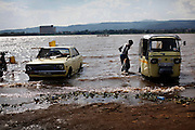 People line up their vehicles to wash them in Lake Victoria in Kisumu, Kenya.  Access to clean water is a problem for many in Kisumu, and waterborne diseases are a common problem.