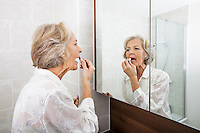 Senior woman applying lipstick while looking at mirror in bathroom