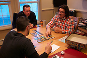Justin King explains the rules of Dominion, a somewhat complicated card game, to his friends, Chris Meier and Matthew Becker.  The Long Island trio usually prefers to start with less complicated games like Zombie Dice, which can be finished in less than 20 minutes.  Then they play lengthier, more complex games.  December 7, 2013.  Photo by Andrew Welsch/NYCity Photo Wire