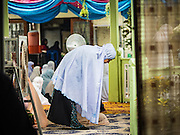 06 JULY 2016 - BANGKOK, THAILAND:  A woman lays out her prayer rug before Eid services at Ton Son Mosque in the Thonburi section of Bangkok. Eid al-Fitr is also called Feast of Breaking the Fast, the Sugar Feast, Bayram (Bajram), the Sweet Festival or Hari Raya Puasa and the Lesser Eid. It is an important Muslim religious holiday that marks the end of Ramadan, the Islamic holy month of fasting. Muslims are not allowed to fast on Eid. The holiday celebrates the conclusion of the 29 or 30 days of dawn-to-sunset fasting Muslims do during the month of Ramadan. Islam is the second largest religion in Thailand. Government sources say about 5% of Thais are Muslim, many in the Muslim community say the number is closer to 10%.       PHOTO BY JACK KURTZ