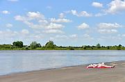Nederland, 4-6-2013 Een jonge vrouw ligt in bikini te zonnen op deze mooie en warme dag op de rand van de kade langs de rivier de IJssel, de IJsselkade. Foto: Flip Franssen/Hollandse