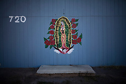 A painting of the Virgin de Guadalupe is painted on the side of a house in Las Cruces, New Mexico.