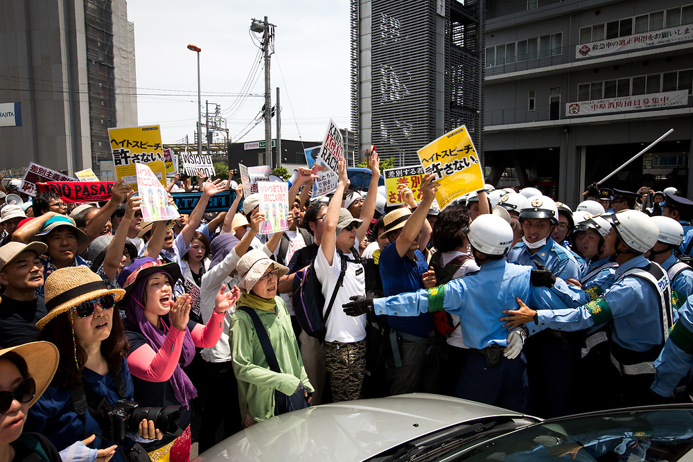 KAWASAKI, JAPAN - JULY 16: Anti-racist groups (L) tried to block Japanese nationalists from marching on the street during a counter-protest rally demanding an end to hate speech in Kawasaki City, Kanagawa prefecture, Japan on July 16, 2017. Scuffles erupted during a counter-protest on racism in Kawasaki City's Nakahara on Sunday, during a right-wing activists attempt to march with their slogans, flags, racist speech, forcing police to intervene. (Photo by Richard Atrero de Guzman/NUR Photo)