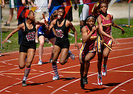 9 APRIL 2011 -- UNIVERSITY CITY, Mo. -- Hazelwood East HIgh School's girls' 100 meter relay team surges into the lead past the team from Hazelwood Central as the teas completed the final exchange of the race at the Charlie Beck Invitational track meet at University City High School in University City, Mo. Saturday, April 9, 2011. Padgett won the event. Hazelwood East's Shayla Luckett (right) passes the baton to teammate Tiana Valentine as Hazelwood Central's Brianna Smith (second from left) passes to her teammate Prenecia Ponds. Hazelwood East won the race. Image (c) copyright 2011 Sid Hastings.