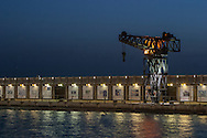 Tel Aviv Port at night, with a crane and storage units illuminated.