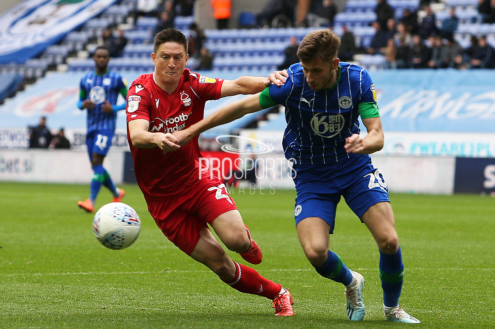Nottingham Forest midfielder Joe Lolley (23) and Wigan Athletic midfielder Joe Williams (20) challenge for the ball during the EFL Sky Bet Championship match between Wigan Athletic and Nottingham Forest at the DW Stadium, Wigan, England on 20 October 2019.
