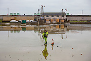 A man dressed in hi-vis working for Sweeptech supervises the cleaning out of rubbish and silt from the bottom of Hove Lagoon, Kingsway,  Hove, East Sussex, United Kingdom. <br />  (photo by Andrew Aitchison / In pictures via Getty Images)