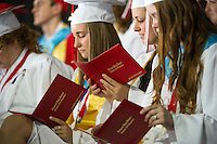 Rachel Weeks and her fellow graduates take a glance at their diplomas during their graduation ceremony at Meadowbrook Pavilion Sunday morning.  (Karen Bobotas/for the Laconia Daily Sun)