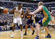 Feb. 21, 2012; Indianapolis, IN, USA; Indiana Pacers shooting guard Paul George (24) dribbles the ball against New Orleans Hornets shooting guard Marco Belinelli (8) and New Orleans Hornets center Chris Kaman (35) at Bankers Life Fieldhouse. Indiana defeated New Orleans 117-108. Mandatory credit: Michael Hickey-US PRESSWIRE