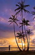 Coconut palm trees and man photographing sunrise at Punalu'u Beach Park, Windward Oahu, Hawaii.