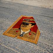 A tapestry of Muammar Gaddafi's portrait lays on the road near a checkpoint in Sebratha.