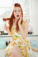 Portrait of a surprised young woman with hair tangled in whisk sitting on kitchen counter