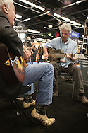 "January 21, 2016 - Anaheim, CA: Grammy award winning US blues musician Mike Dowling (gray shirt) and world touring US bluesman Doug Macleod (black jacket, jeans & snakeskin boots) jam at the National Resophonic booth during the NAMM Show, an annual trade show organized by the The National Association of Music Merchants (NAMM). <br /> <br /> The largest of its kind, NAMM features music instruments and products of every imaginable music-related item. National Resophonic was started in 1989 by Don Young and McGregor Gaines in a garage in Long Beach, CA. The two resurrected the legendary guitar company National String Instrument Corporation originally founded in 1927 by the Slovakian born John Dyoperra. These instruments called ""resonator guitars"" were steel bodied with built in speaker cones that projected loud sound, good enough for live performances. Their unique sound became the preferred instrument of blues, Hawaiian and hillbilly musicians of the 1930s and are iconic of these musical genres. National went out of business in the 1950s due to the invention of the electric guitar. In 1990, Young and Gaines formed National Resophonic, a new company in San Louis Obispo, CA that produced excelent modern versions of the older guitars. Their guitars are in very high demand worldwide among guitarists from street performers to famed musicians like Keb' Mo', Bonnie Raiit, John Mellencamp and Eric Clapton. National currently produces nearly 2700 instruments per year, representing more than 50 different models. The waiting list to order one of their guitars can be several months. Young and Gaines sold their interests in the company which it is now owned by Eric Smith, an emplyee of National for 24 years. Sadly, Don Young passed away on June 15, 2016. (Torin Boyd/Polaris)."
