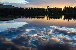 Water lilies and cloud reflections on Lang Pond in Maine's Northern Forest. Cold Stream watershed, Parlin Pond Township.