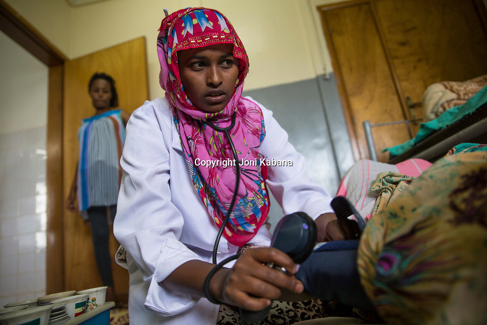 Seada Abdi, 25, helps a patient who is suffering from obstructed labor.