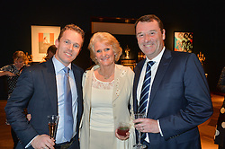 Left to right, ANDREW BUCHANAN and PHILIP & GILL BROOK he is chairman of the All England Club at a party to celebrate the publication of Interiors For Living by Joanna Wood held at Christie's. 8 King Street, St.James's, London on 2nd March 2015.