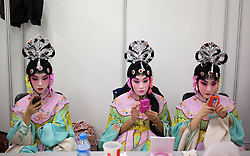 epa02920132 A picture made available on 17 September 2011 of Peking opera performers playing with their mobile phones backstage during the closing ceremony of the first young Peking Opera Actors' Arena contest in Beijing, China on 16 September 2011. Young Peking opera actors from all over the country perform during the closing ceremony of the first young Peking Opera Actors' Arena contest which aims to rejuvenate the traditional cultural art with new blood and form. Peking Opera or Beijing Opera is a traditional Chinese theatre art form that arose in the late 18th century that was made popular in the Qing Dynasty court and has come to be deemed as one of the cultural treasures of China.  EPA/HOW HWEE YOUNG