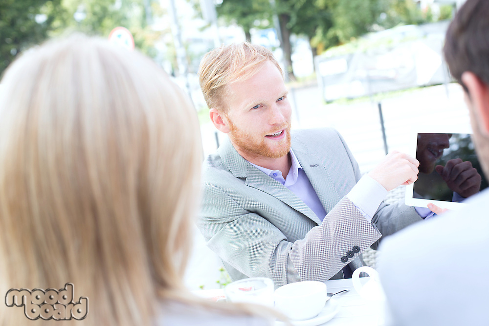 Businessman discussing over digital tablet with colleagues at sidewalk cafe