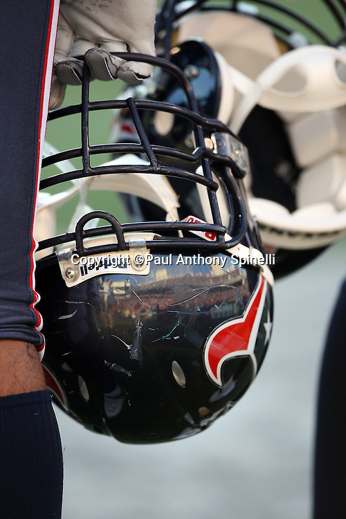 A Houston Texans player holds a scratched up helmet during the NFL football game against the Buffalo Bills, November 1, 2009 in Orchard Park, New York. The Texans won the game 31-10. (©Paul Anthony Spinelli)