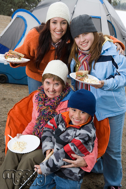 Family eating in front of a tent