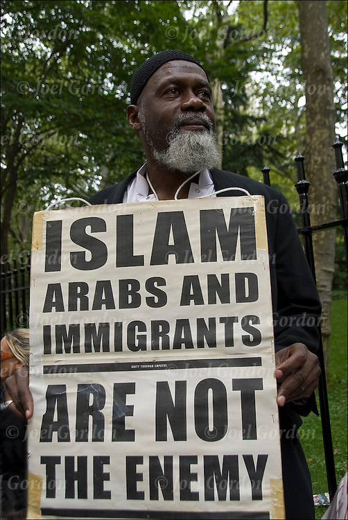 "September 11 Rally against racism and Islam phobia to stop the attacks on the Muslim community. Muslim holding sign ""Islam Arabs and Immigrants Are Not The Enemy"" listening to speaker."