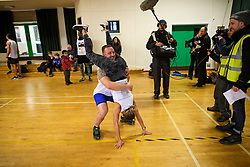 © Licensed to London News Pictures. 03/03/2019. Dorking, UK. Competitors are watched by media as they prepare to take part in the 2019 annual Wife Carrying Race in Dorking, Surrey. Run over a course of 380m, with both men and women carry a 'wife' over obstacles, the race is believed to have originated in the UK over twelve centuries ago when Viking raiders rampaged into the northeast coast of England carrying off any unwilling local women . Photo credit: Ben Cawthra/LNP