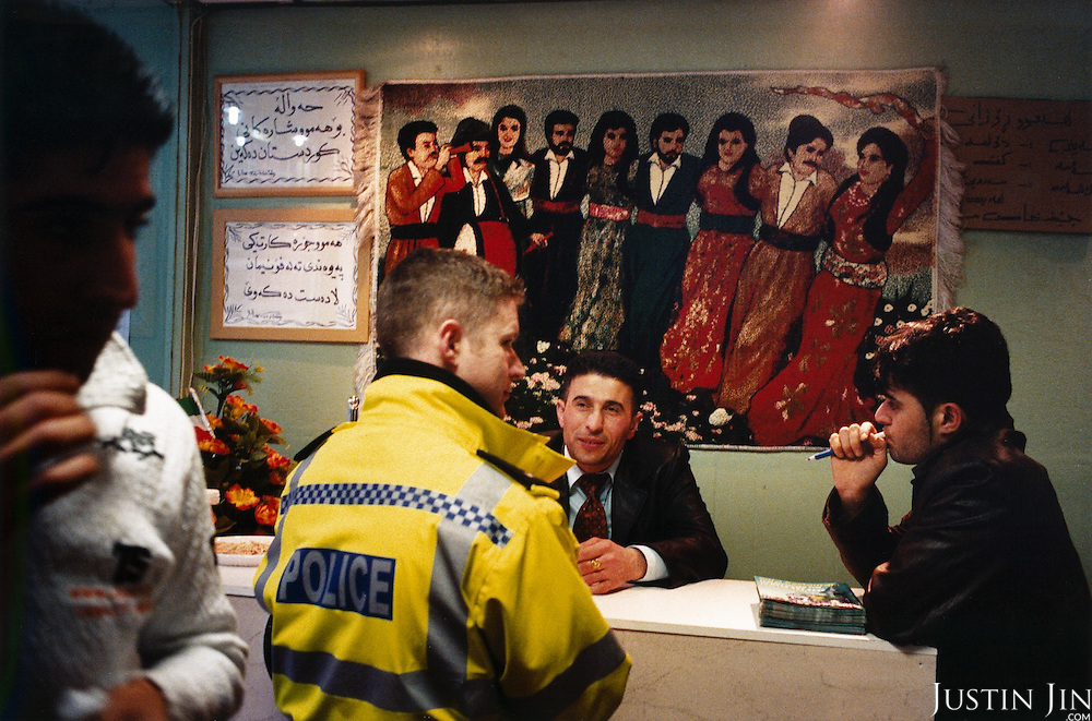 Police officers arrest a man suspected of robbery in Leicester city's Somali neighbourhood. A passerby looks on. ..Leicester has a large Somali population that migrated from the Netherlands en masse several years ago. ..Leicester is expected to be the first city in the UK to have a majority non-white population within the next few years. It is one of the most ethnically-diverse cities in Europe. ....Picture taken April 2005 by Justin Jin