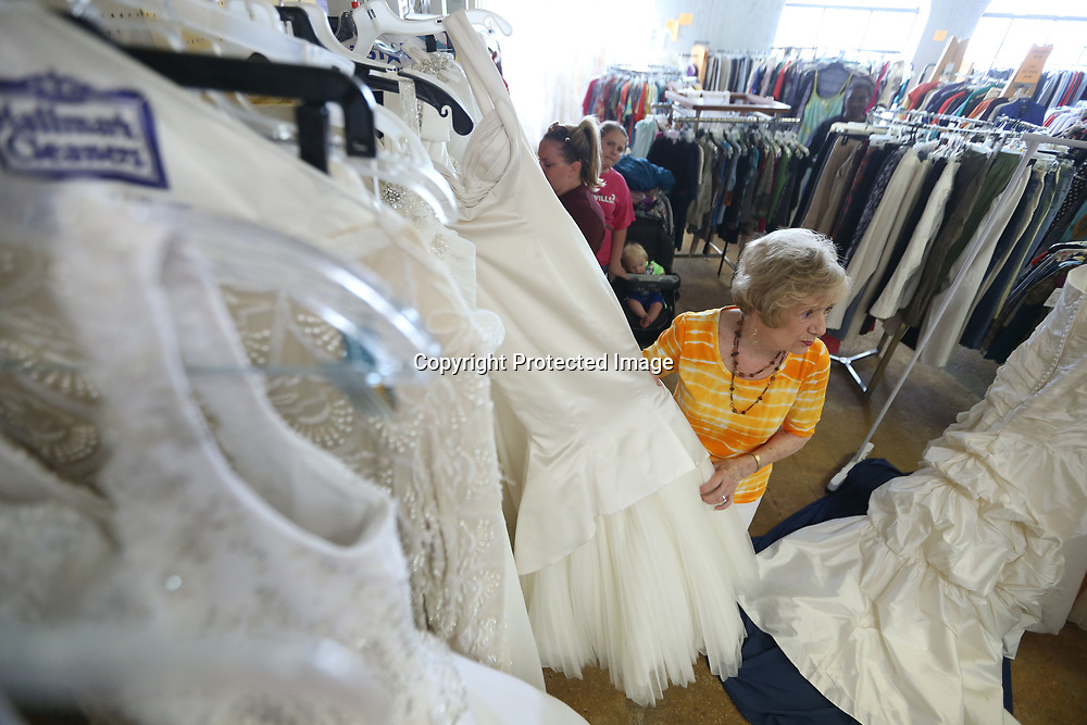 Cherie Harris, a volunteer at the Sanctuary Village Shoppe, pulls a wedding dress from the rack on Thursday afternoon in Tupelo. The thrift store that benefits the Sanctuary Hospice House gets a surprising number of wedding dresses which they sell for $50.00.