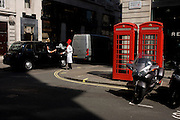 A sandwich shop chef in red hat hands out meal deal information beside two red London telephone box kiosks.