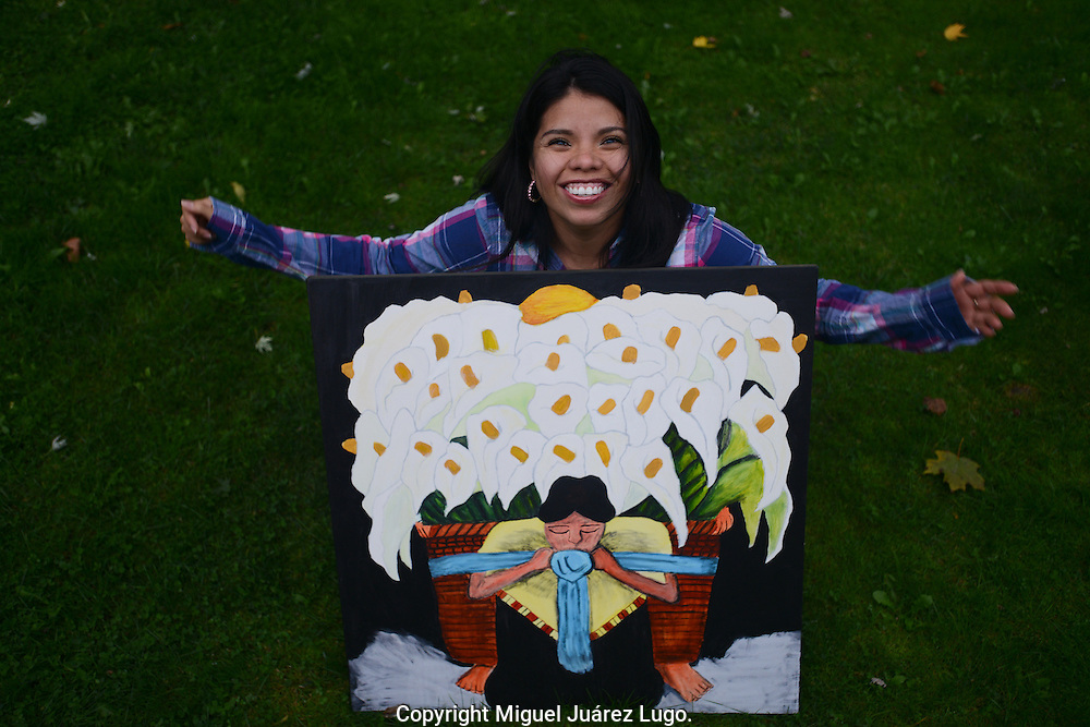 "PAINESVILLE, OH - OCT. 15, 2012. Maria Nancy Pacheco, 25, with a painting she did--a copy of a Diego Rivera--when she was struggling with her identity as a Mexican who was becoming American. She arrived in the US when she was 17 from San Francisco del Rincon in state of Guanajuato, Mexico and became US citizen on January 6, 2012. She plans to vote for the first time in November. She feels strongly inclined for the Obama-Biden ticket, though she is disappointed that Obama has not done more for Latino immigrants. She said she is tired that Latinos have to live in the shadows. ""I'm going to vote and I hope with that I can vote for so many that can't do it,"" said Pacheco, who works in a factory that makes wax mold bases for airplane parts. (Photo by Miguel Juárez Lugo)"