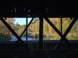 View of the Upper Ammonoosuc River in Fall from the covered bridge (1857)  in Stark, New Hampshire. Bridge is of the Paddleford truss-style of construction.