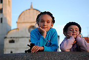 Two children (9 years old, 5 years old), resting on wall, Church of St. Mary (Crkva Sveti Marije) in background, in late afternoon sunlight. Zadar, Croatia