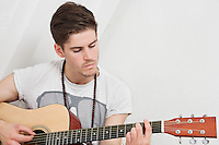 Young Caucasian man playing guitar