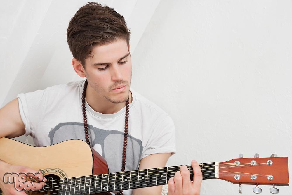 Young Caucasian man playing guitar
